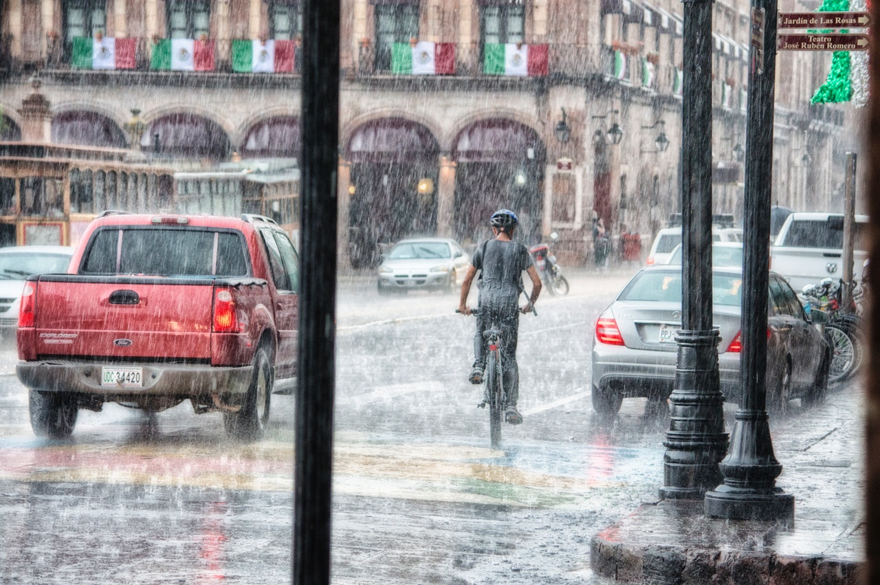 person-riding-a-bicycle-during-rainy-day-763398